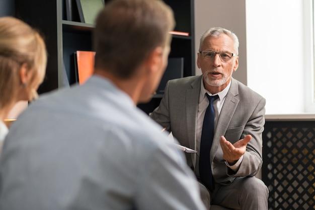 Confiado psicoterapeuta apuesto profesional que consulta a una pareja casada sentada en su oficina y escuchándolo