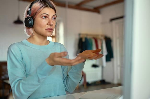 Confianza y elegante joven mujer de cabello rosa con auriculares inalámbricos y un anillo en la nariz que gesticula emocionalmente mientras realiza un seminario web a través del chat de videoconferencia en cumputer.