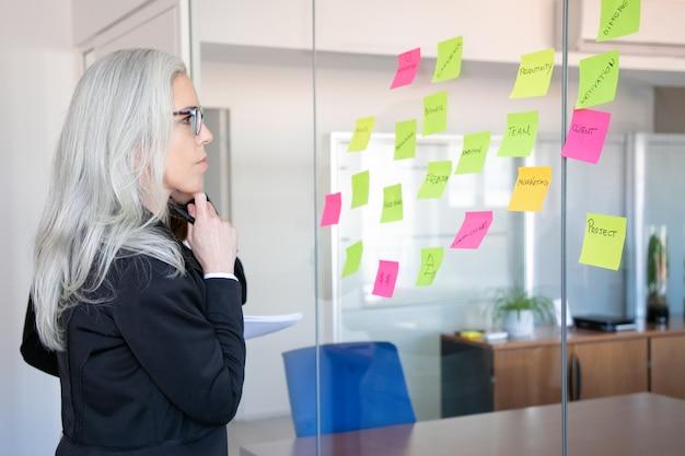 Confianza empresaria concentrada mirando pegatinas en la pared de vidrio. trabajadora de pelo gris concentrada pensando en notas para la estrategia del proyecto. concepto de marketing, negocios y gestión