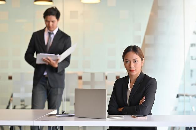 Confianza empresaria joven sentado en el lugar de trabajo de negocios con el equipo.