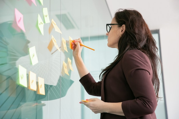 Confianza empresaria de mediana edad escribiendo en la etiqueta engomada con lápiz y lluvia de ideas