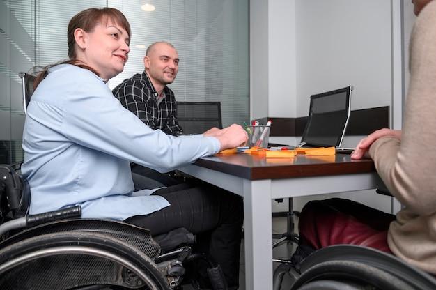 Confianza empresaria en silla de ruedas en el escritorio
