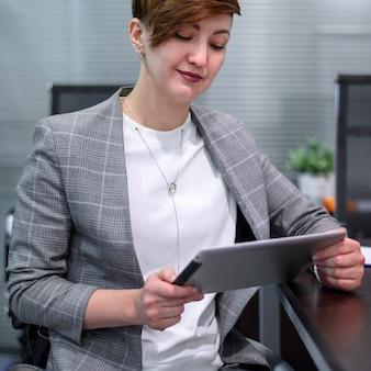 Confianza empresaria en silla de ruedas trabajando en tableta