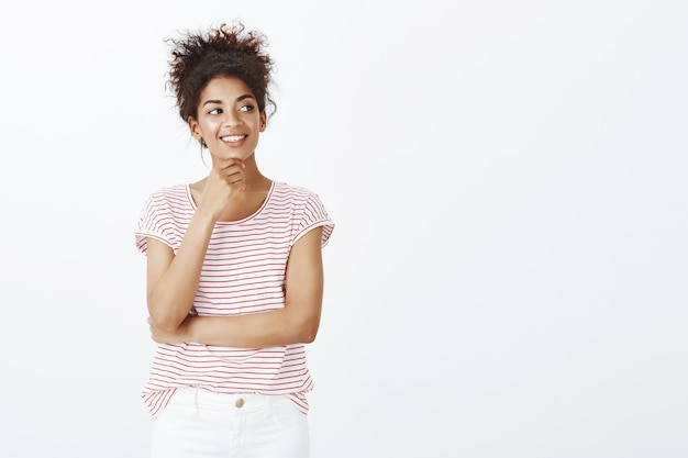 Confianza encantadora mujer con peinado afro posando en el estudio