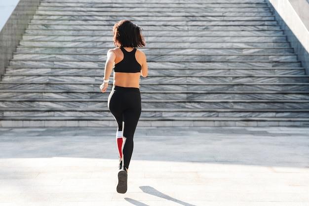 Confianza joven deportista corriendo por las escaleras al aire libre