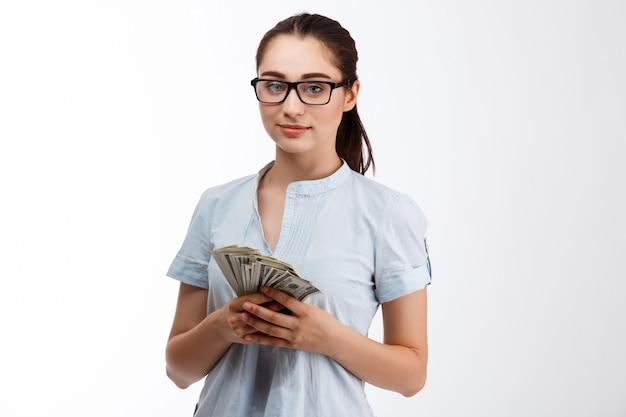 Confianza joven hermosa chica de negocios en vasos con dinero sobre pared blanca