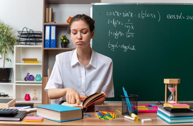 Confianza joven profesora de matemáticas sentada en un escritorio con útiles escolares apuntando con el dedo sobre el libro abierto y mirándolo en el aula