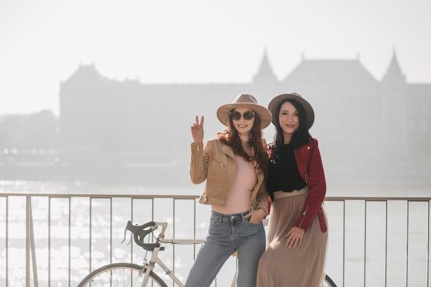 Confianza mujer jengibre posando junto a la mujer de pelo negro y mostrando el signo de la paz