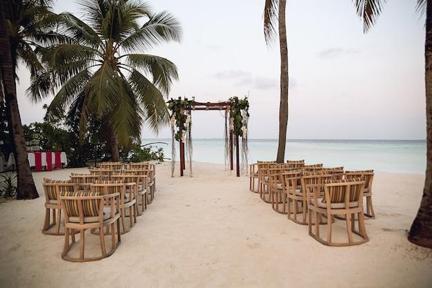 Configuración de boda en la playa, recepción de boda tropical al aire libre, arco de boda