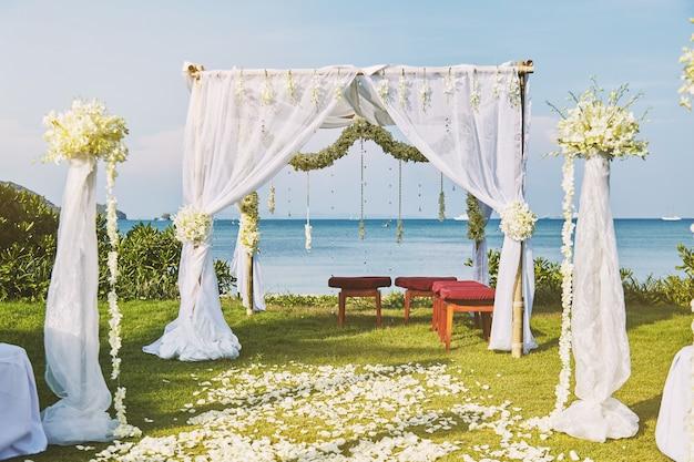 Configuración hermosa del arco de la flor de la boda de playa para el lugar de la boda con vista al mar panorámica