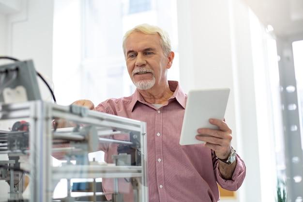 Configuración importante. trabajador senior guapo cambiando la configuración de una impresora 3d mientras sigue las instrucciones en su mesa