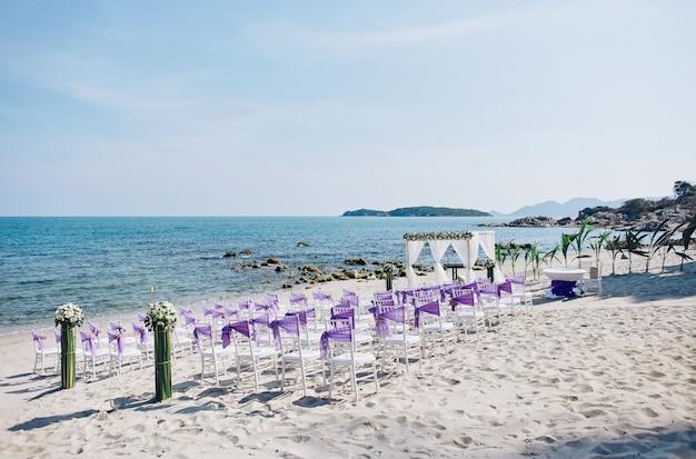 Configuración del lugar de la boda en la playa con sillas de chiavari blanco decoración con organza púrpura sas