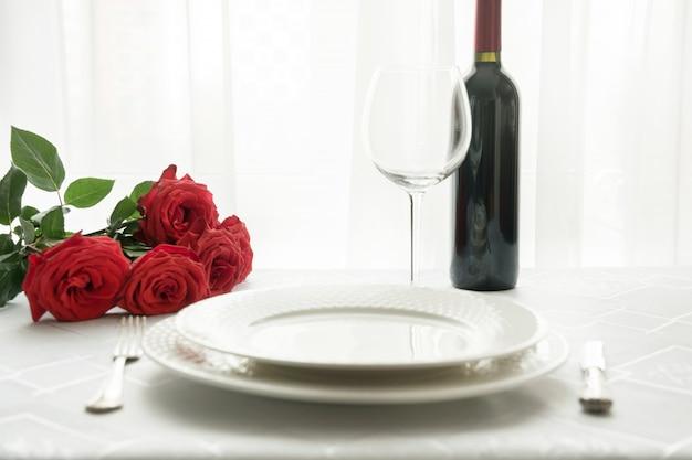 Configuración de lugar de mesa de día de san valentín con ramo rosas rojas y vino.