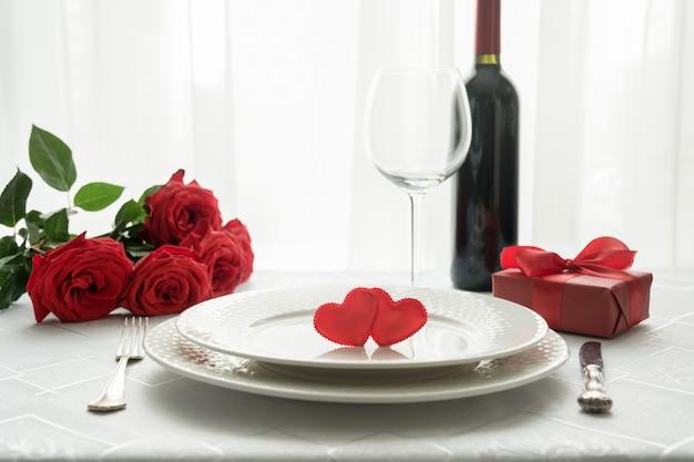 Configuración del lugar de la mesa del día de san valentín con rosas rojas, caja de regalo y vino. invitación para una fecha.