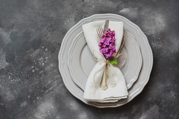 Configuración de lugar de mesa con flores lilas púrpuras, cubiertos sobre fondo vintage.