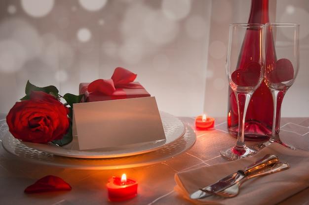 Configuración del lugar de la tabla del día de tarjetas del día de san valentín con las rosas rojas y el champán. invitación para una fecha.