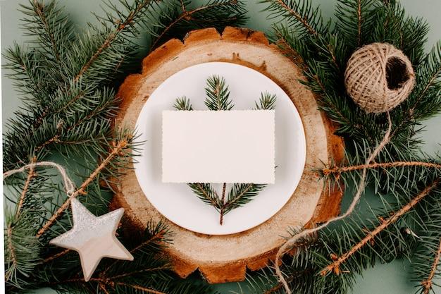 Configuración de mesa de estilo natural de maqueta festiva de navidad con tarjeta vacía