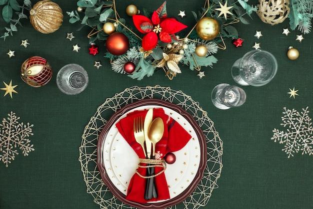 Configuración de mesa navideña con platos blancos rojo oscuro, anillo de papel rojo y flor de pascua, utensilios dorados. decoraciones doradas rojas, verdes y doradas.