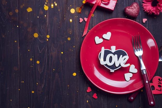 Configuración de la mesa romántica en mesa de madera marrón. plantilla de tarjeta de día de san valentín
