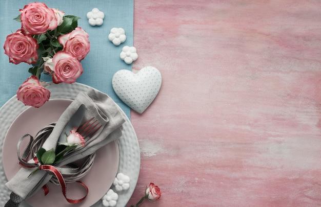 Configuración de la mesa de san valentín, cumpleaños o aniversario, vista superior sobre fondo rosa claro, espacio de copia