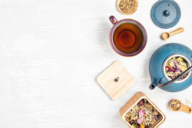 Configuración tradicional de la ceremonia del té, tetera y taza de té con té de hierbas y frutos secos. desintoxicación de tisana, relajación, curación, reconfortante saludable, concepto de la hora del té. vista superior, endecha plana