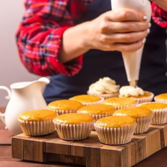 Confitero femenino en un delantal azul y una camisa roja a cuadros aplica crema a los cupcakes