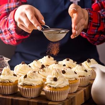 Confitero mujer decora cupcakes