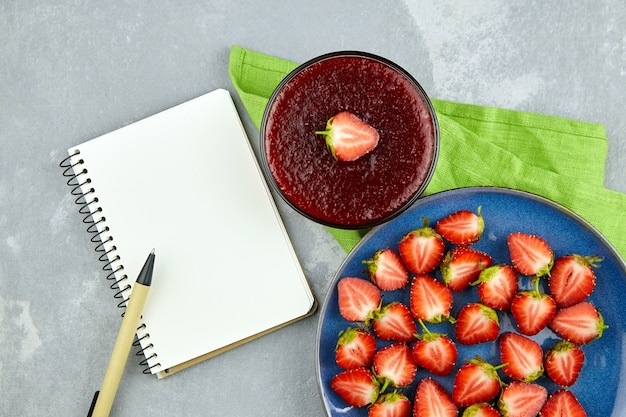 Confitura de fresa con bayas frescas en placa azul, bloc de notas y bolígrafo sobre mesa gris