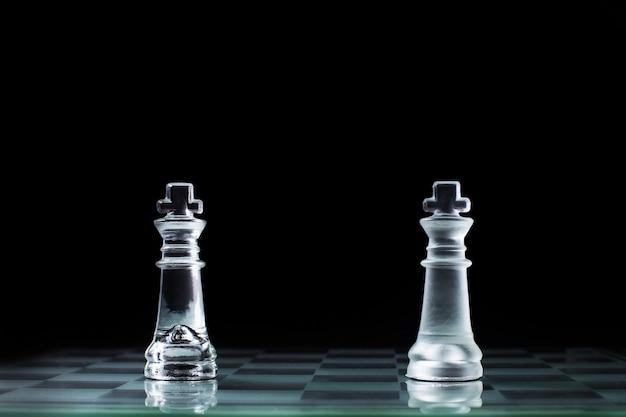 Confrontación - dos rey de ajedrez de madera de pie uno contra el otro en un tablero de ajedrez.