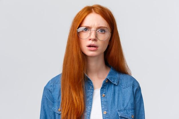 Confundida y disgustada, insegura pelirroja con gafas conversando, hablando parece frustrada y poco convencida, tiene dudas con el ceño fruncido