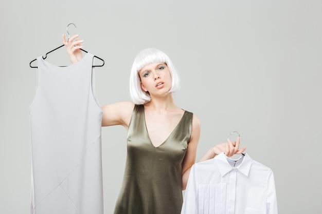 Confundida hermosa joven eligiendo entre camisa y vestido
