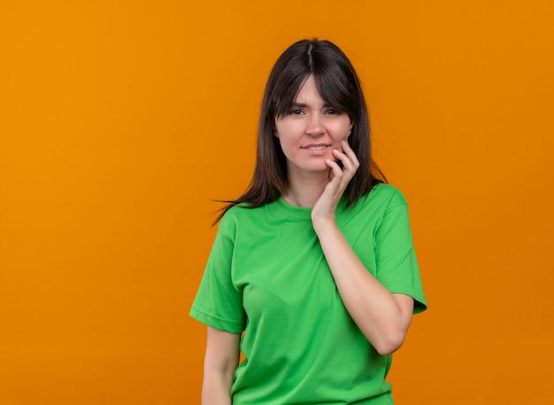 Confundida joven caucásica en camisa verde pone la mano en la barbilla y mira a la cámara sobre fondo naranja aislado con espacio de copia