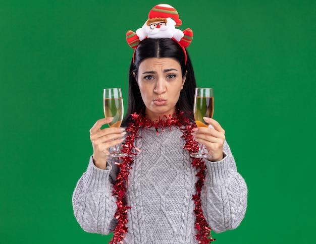 Confundida joven caucásica con diadema de santa claus y guirnalda de oropel alrededor del cuello sosteniendo dos copas de champán mirando a cámara aislada sobre fondo verde