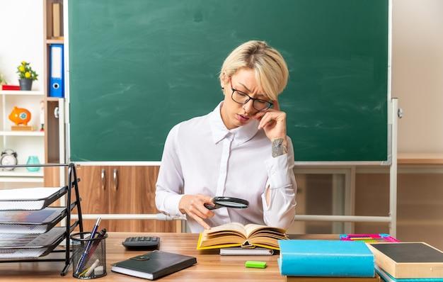 Confundida joven profesora rubia con gafas sentado en el escritorio con herramientas escolares en el aula mirando el libro abierto a través de una lupa tocando la cabeza