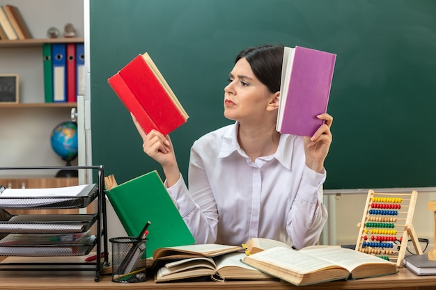 Confundida joven profesora sosteniendo y leyendo el libro sentado a la mesa con herramientas escolares en el aula