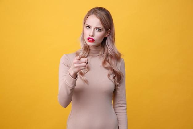 Confundida jovencita rubia con labios de maquillaje brillante señalando