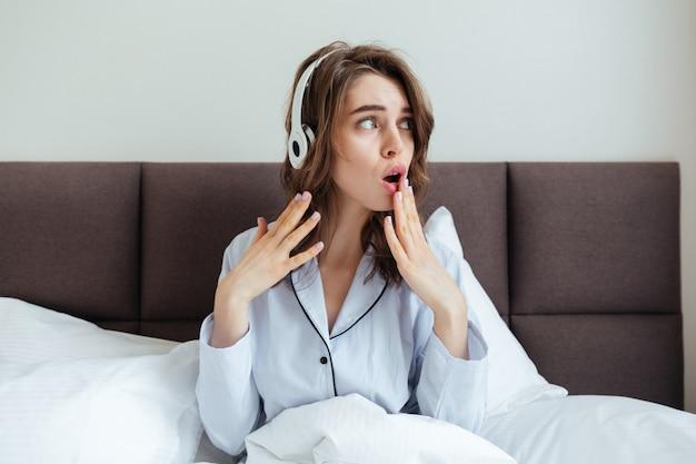 Confundida jovencita vestida con pijama escuchando música.