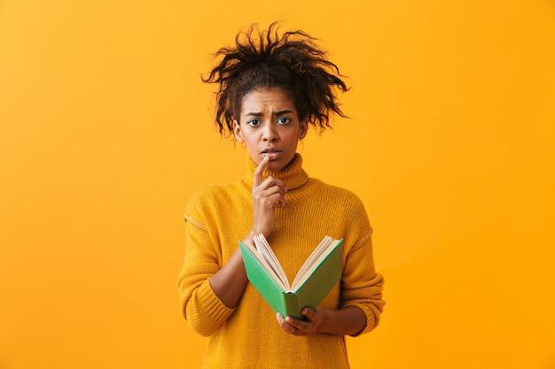 Confundida mujer africana vistiendo suéter sosteniendo un libro aislado