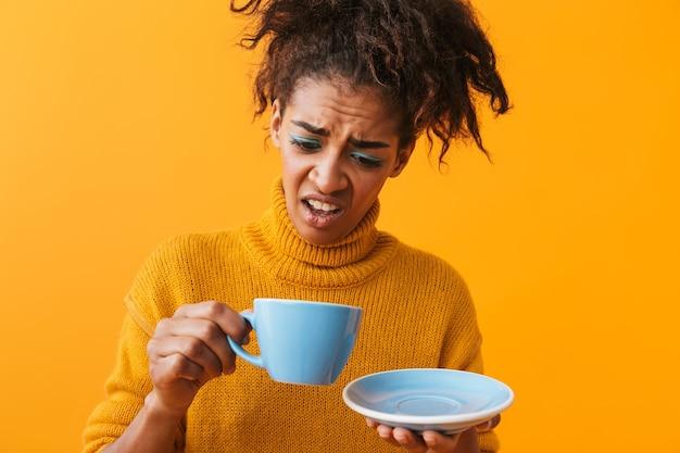 Confundida mujer africana vistiendo suéter sosteniendo la taza en el platillo aislado