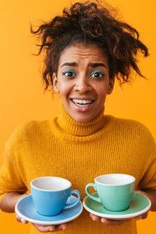 Confundida mujer africana vistiendo suéter sosteniendo tazas en platillos aislado
