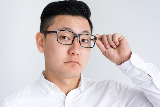Confundido hombre asiático ajustando gafas