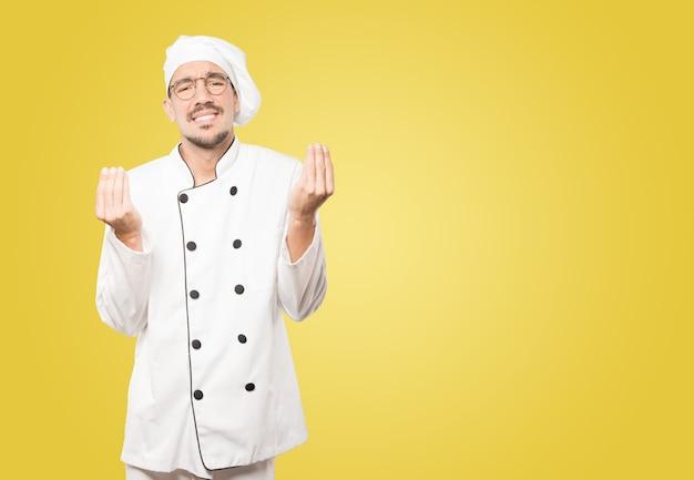 Confundido joven chef haciendo un gesto italiano de no entender