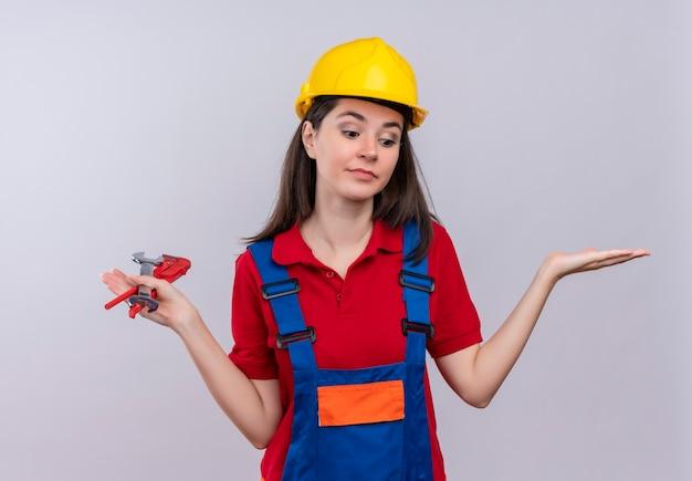 Confundido joven constructor tiene llave de tubo y llave de taller sobre fondo blanco aislado