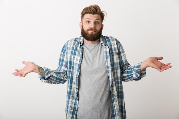 Confundido joven vestido con camisa a cuadros que se encuentran aisladas