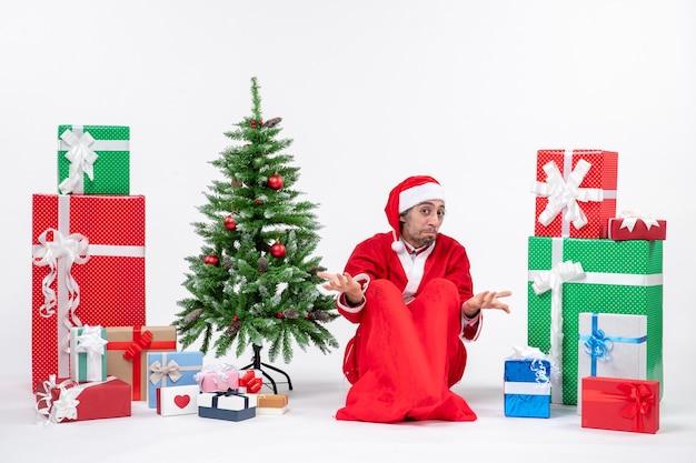 Confundido joven vestido como papá noel con regalos y árbol de navidad decorado sentado en el suelo sobre fondo blanco.