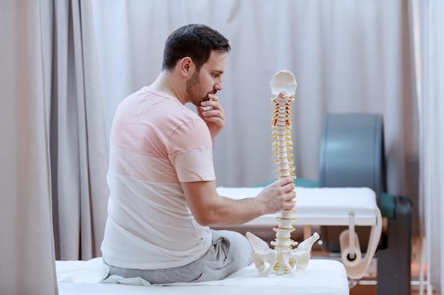 Confundido paciente varón caucásico con modelo de columna vertebral mientras está sentado en la cama de un hospital con la espalda vuelta.