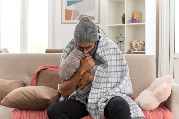 Congelación joven enfermo en gafas ópticas envuelto en cuadros con bufanda alrededor de su cuello con sombrero de invierno abrazando la almohada mirando hacia abajo sentado en el sofá en la sala de estar