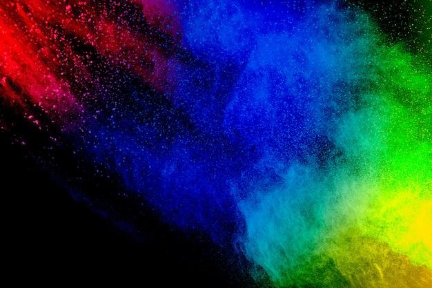 Congelar movimiento de partículas de polvo de colores sobre fondo negro