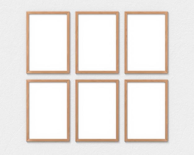 Conjunto de 6 marcos verticales de madera con un borde colgado en la pared. representación 3d