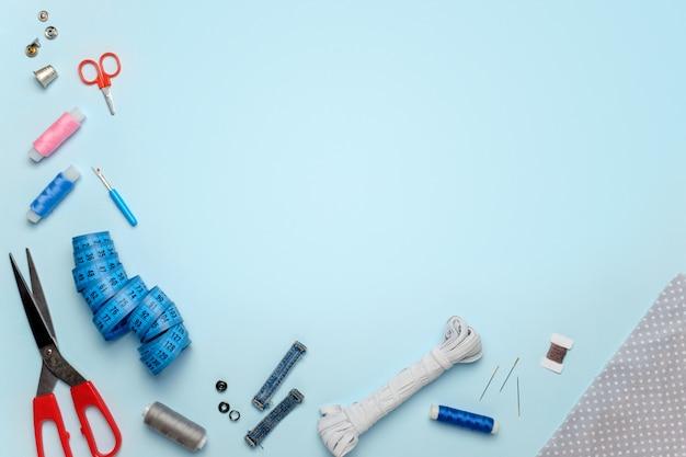 Conjunto de accesorios de costura en un fondo azul, vista desde arriba